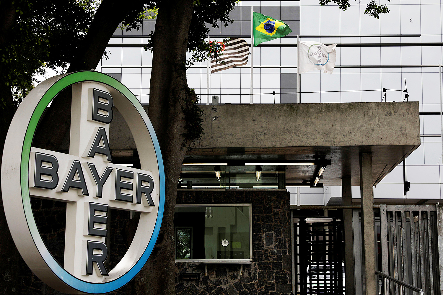 The Brazilian national flag is seen next to Bayer's flag in front of Bayer headquarters in Sao Paulo